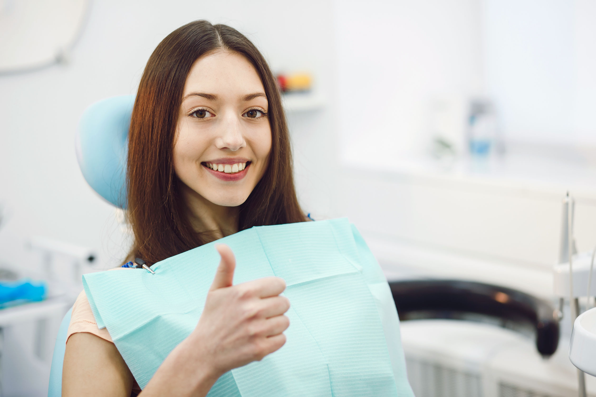 Happy Patient Sits in a Chair at the Dentist